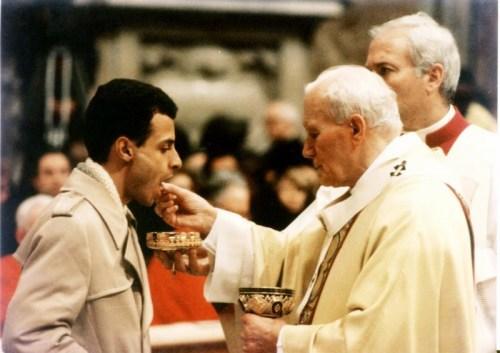Observem o zelo pelo qual o Papa entrega a Eucaristia, existe até outra pessoa com a tampa da âmbula por baixo, para que não se perca nenhuma partícula do corpo de Cristo.